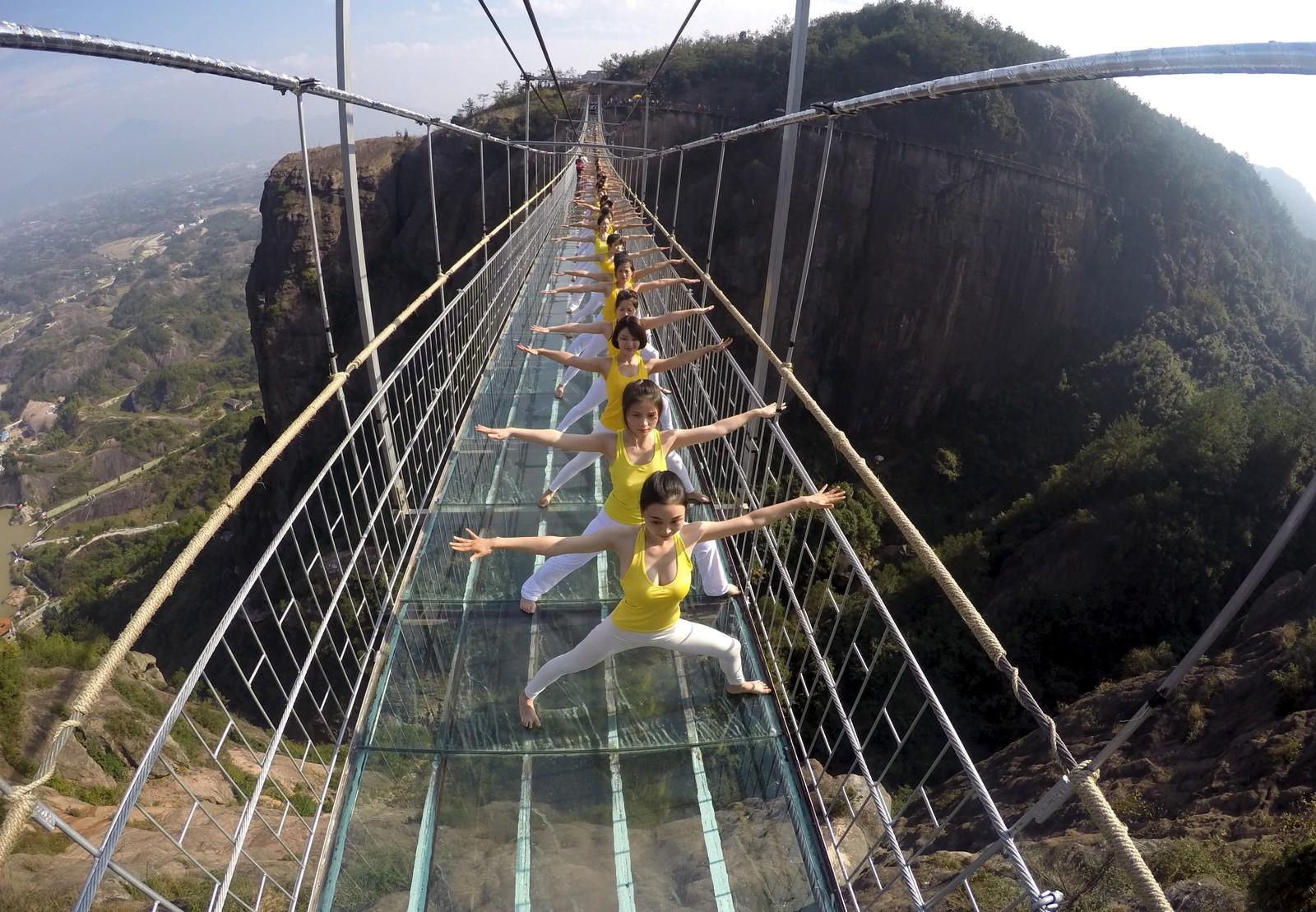 Yoga på en glassbru i en nasjonalpark i Hunan-provinsen i Kina. Rundt hundre deltakere hadde møtt opp for å strekke seg i et luftig miljø.