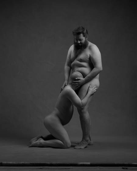 En skallet mann sitter på kne og simulerer oralsex på en annen mann som kraftig bygd. Begge er nakne. Kjønnsorganene er ikke synlige.