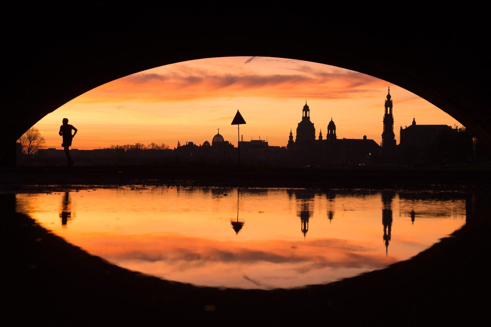 En joggers silhuett krysser broa over elva Elbe i Dresden, Tyskland en tidlig morgen i uka som gikk.