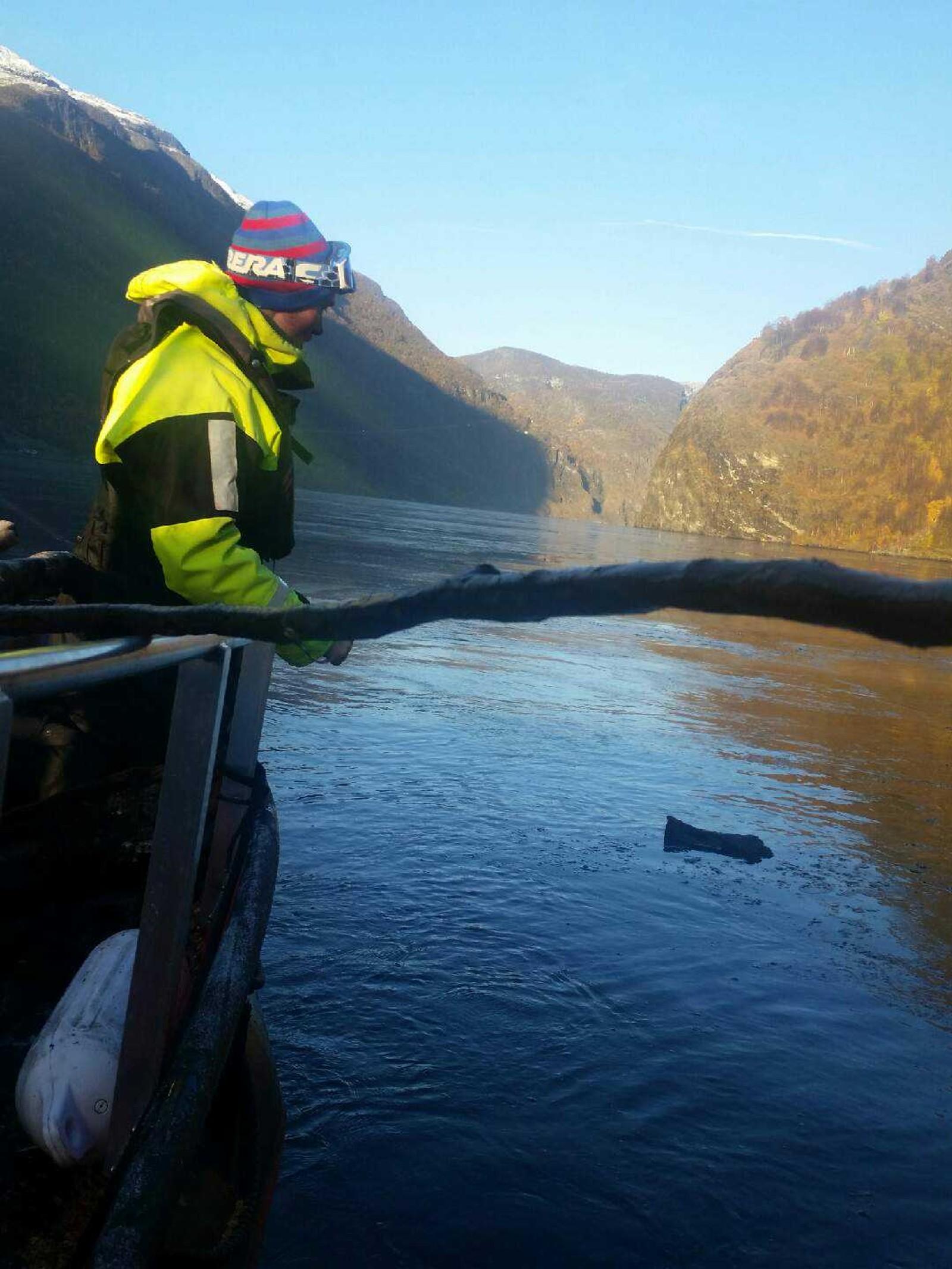RYDDAR: Her plukkar Jonathan Rind Thomsen opp tømmer frå Aurlandsfjorden. - Vi er veldig takksame for at Kystverket er så løsningsingsorienterte at dei lot oss ta arbeidet når vi har kapasitet til å rydde, seier Thomas Rastad i Flåm Guideservice.