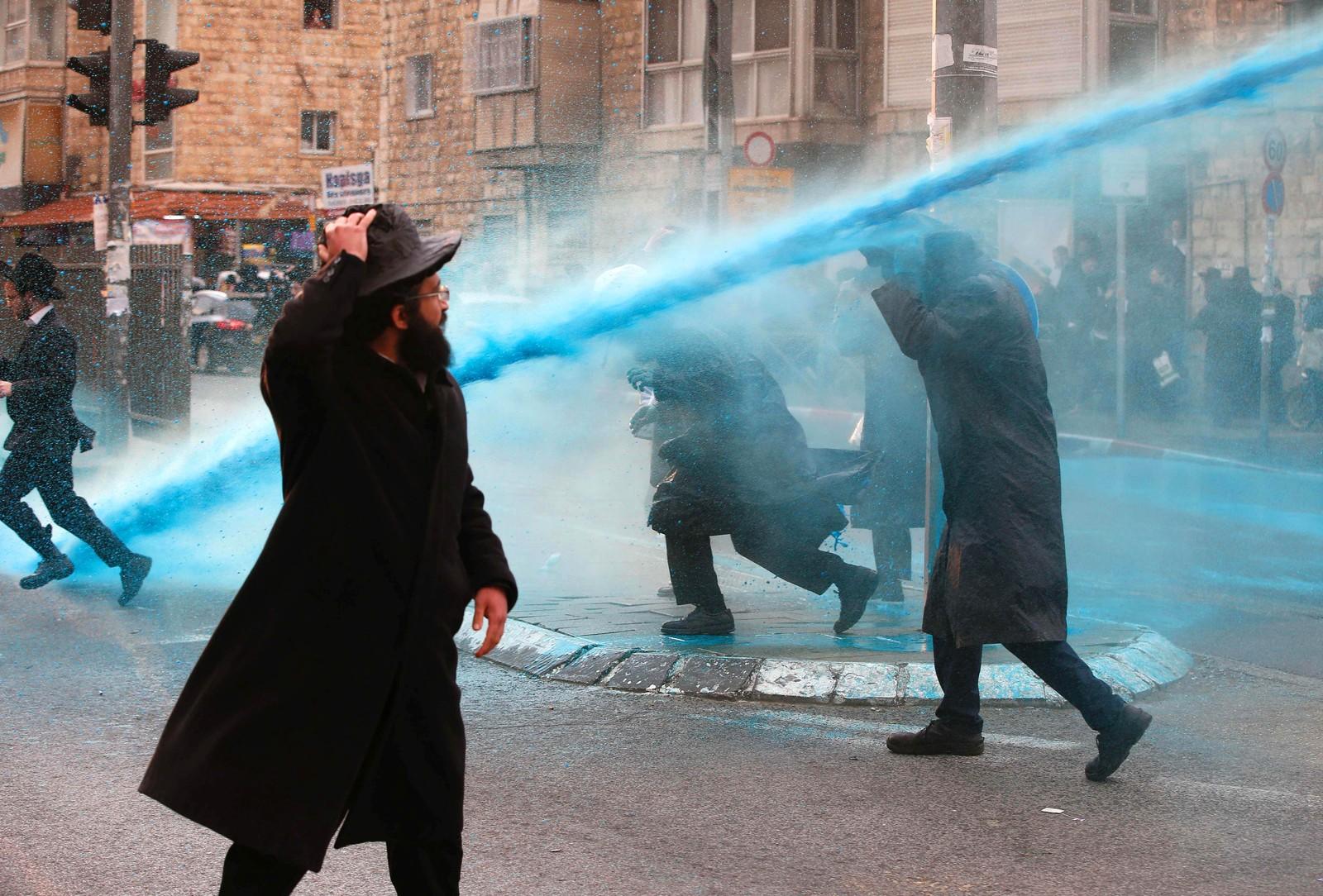Ultraortodokse jøder får gjennomgå under en demonstrasjon mot at også de har verneplikt i den israelske hæren.