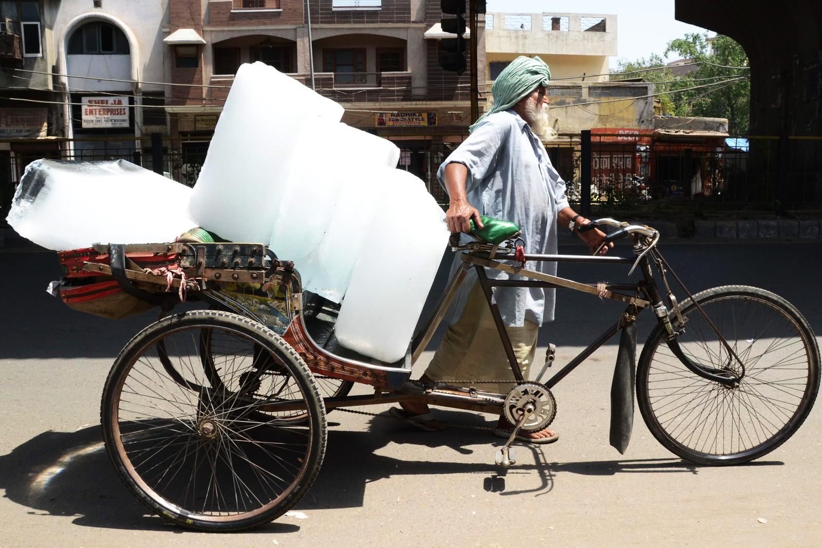 Mann frakter isblokker på sykkel i Amritsar i India.