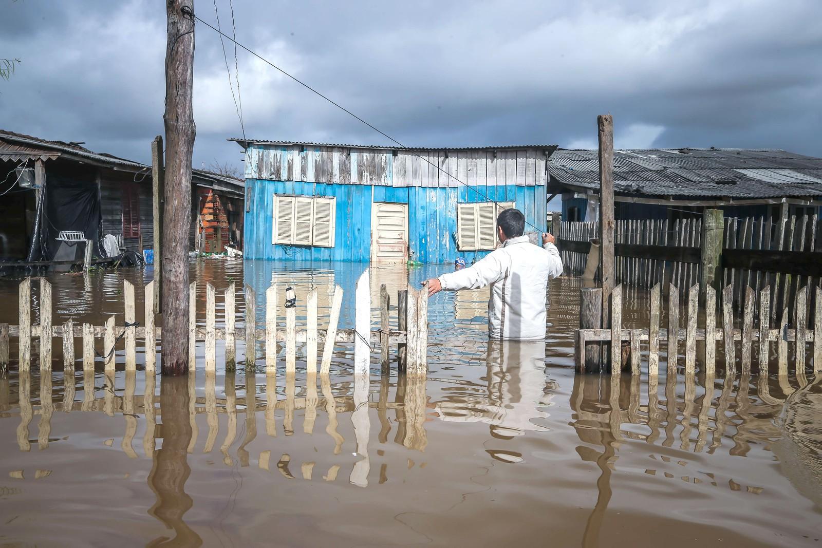 En mann er på vei inn til huset sitt i Villa Rica i Gravatai i Brasil. Store regnmengder i området de siste to ukene har ført til flom flere steder. Nærmere 50.000 mennesker er rammet.