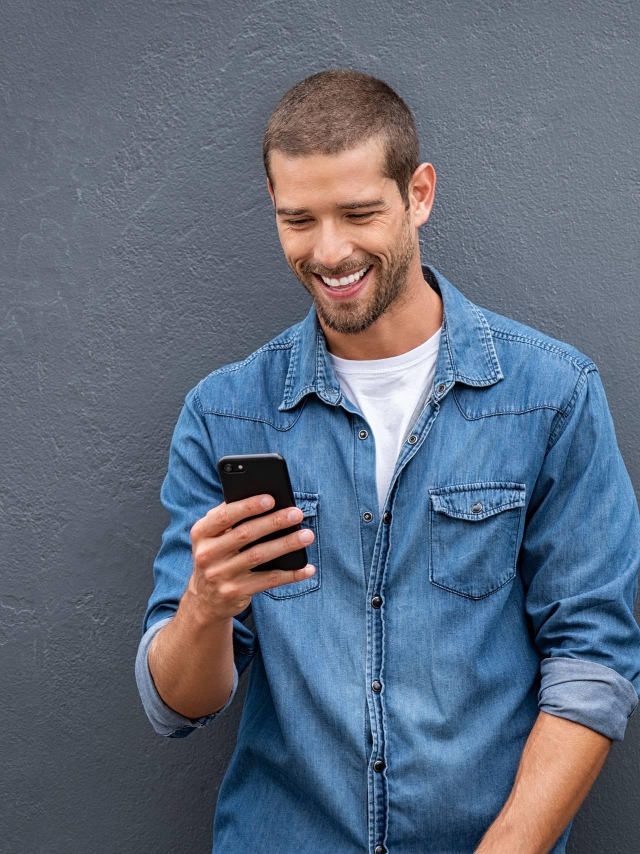 Mann flørter på mobilen.