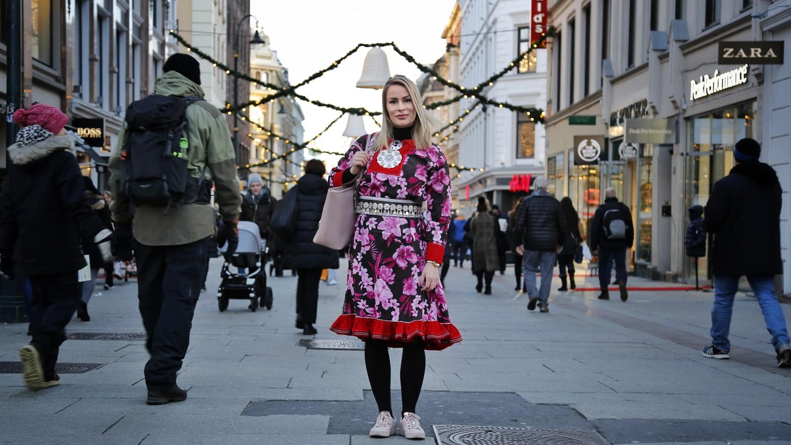 Ung kvinne i blomstrete samedrakt står midt i gata i en by. Hun har to søljer på brystet og belte med sølvknapper, rosa Micahel Kors veske over skulderen og rosa sko.