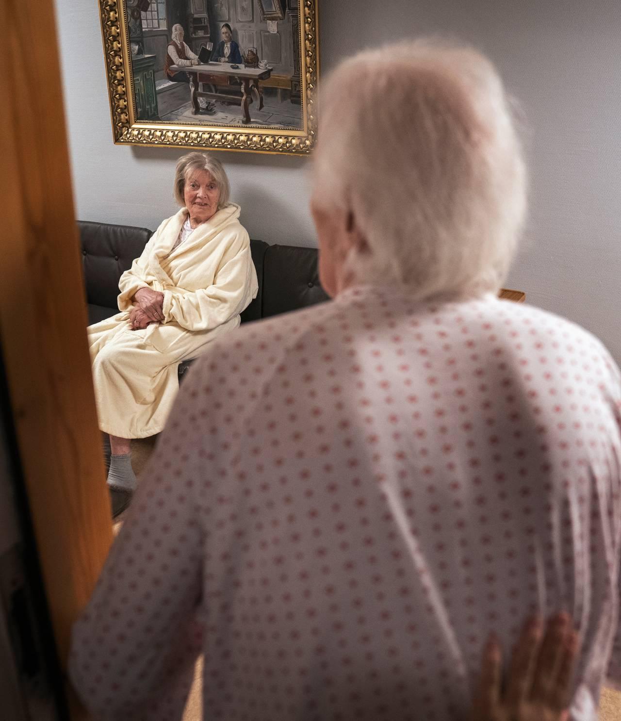 Birger står i døråpningen og møter blikket til Randi, som sitter i sofaen i gangen utenfor.