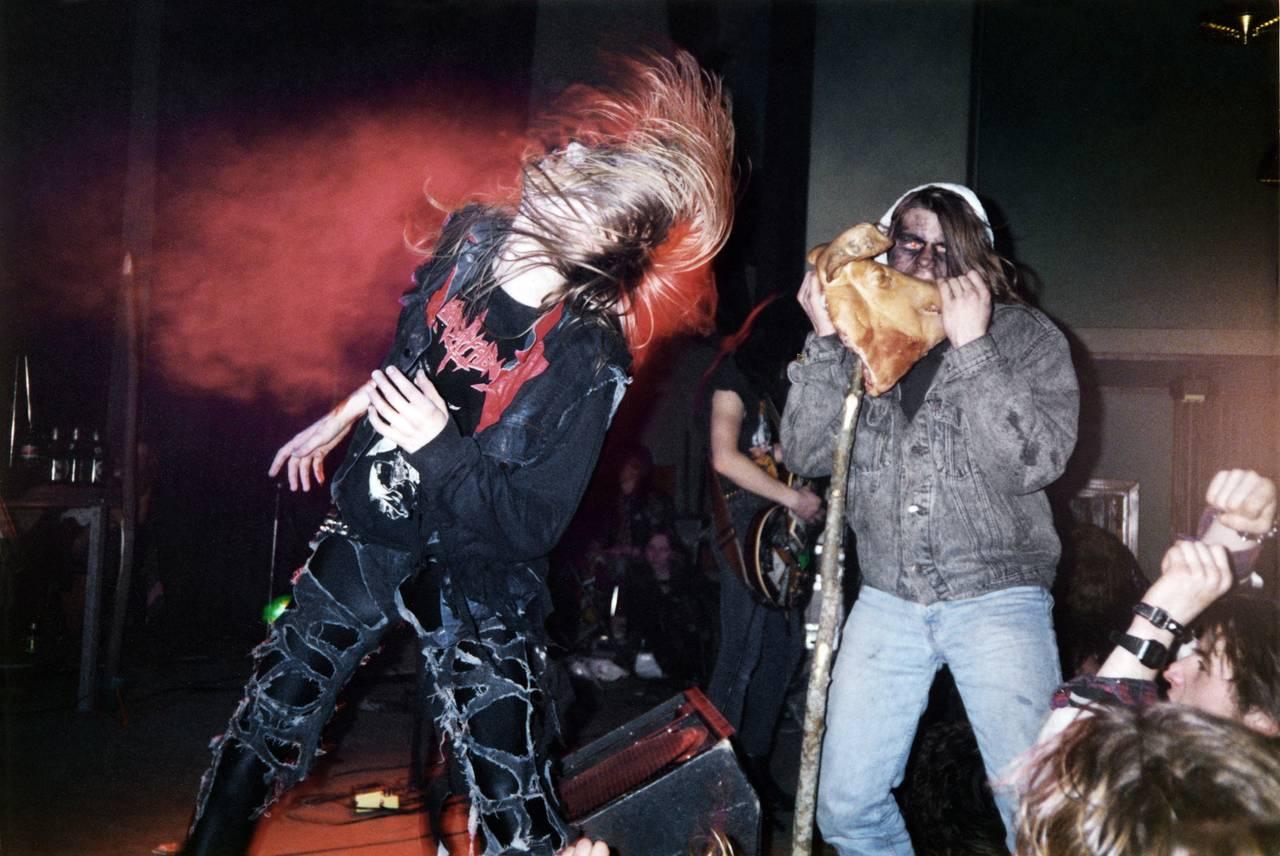 Pelle Ohlin og en ukjent publikummer på scenen under en konsert. Pelle ser ut til å være midt i en headbang, mens publikummeren later som han tar en bit av et speket grisehode bandet har tatt med seg på scenen.