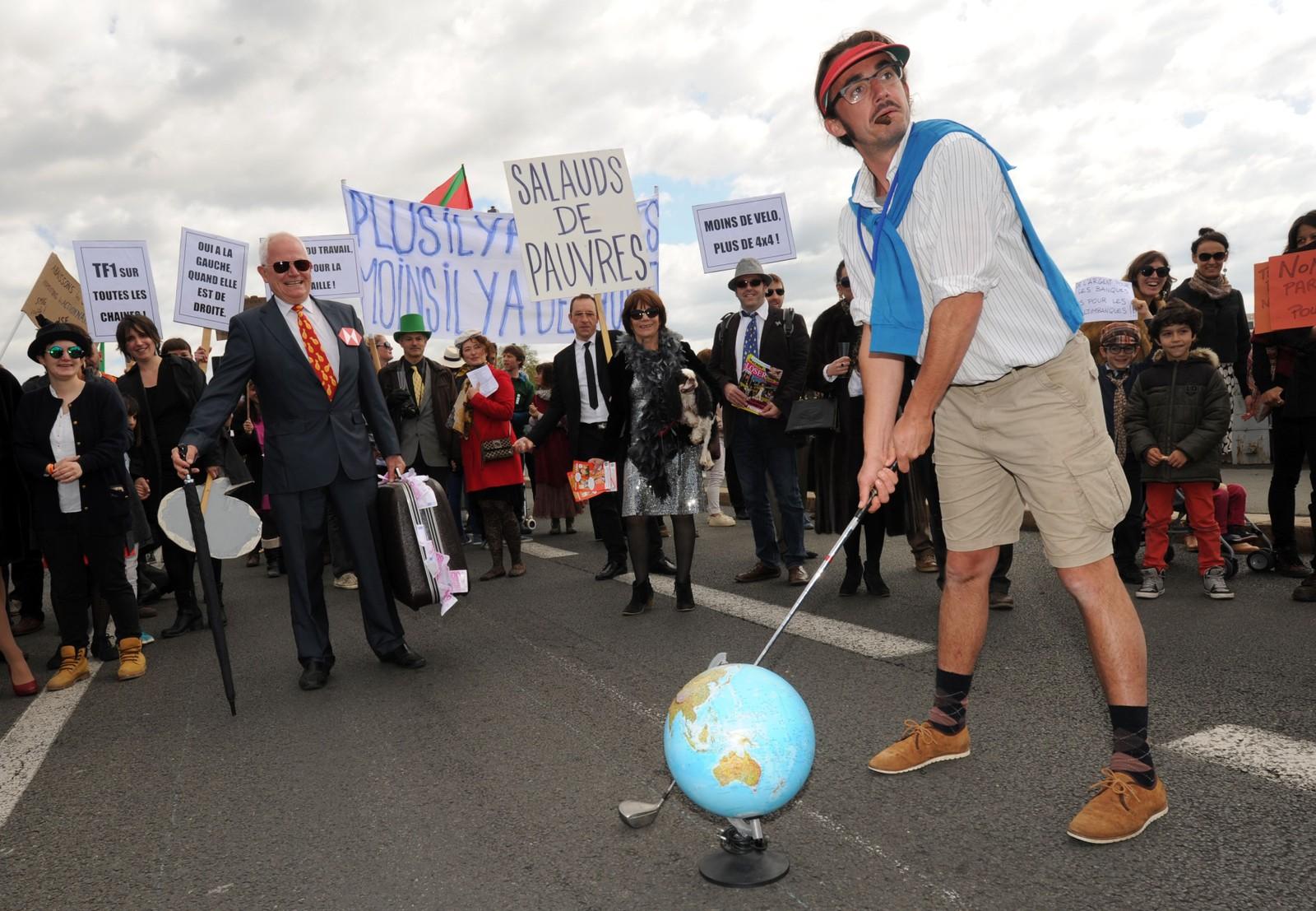 En mann kledd i golfklær tar del i en «rikmannsprotest» for å markere 1. mai i Bayonne i Frankrike. Deltakerne er medlemmer av bevegelsen «Bizi!».