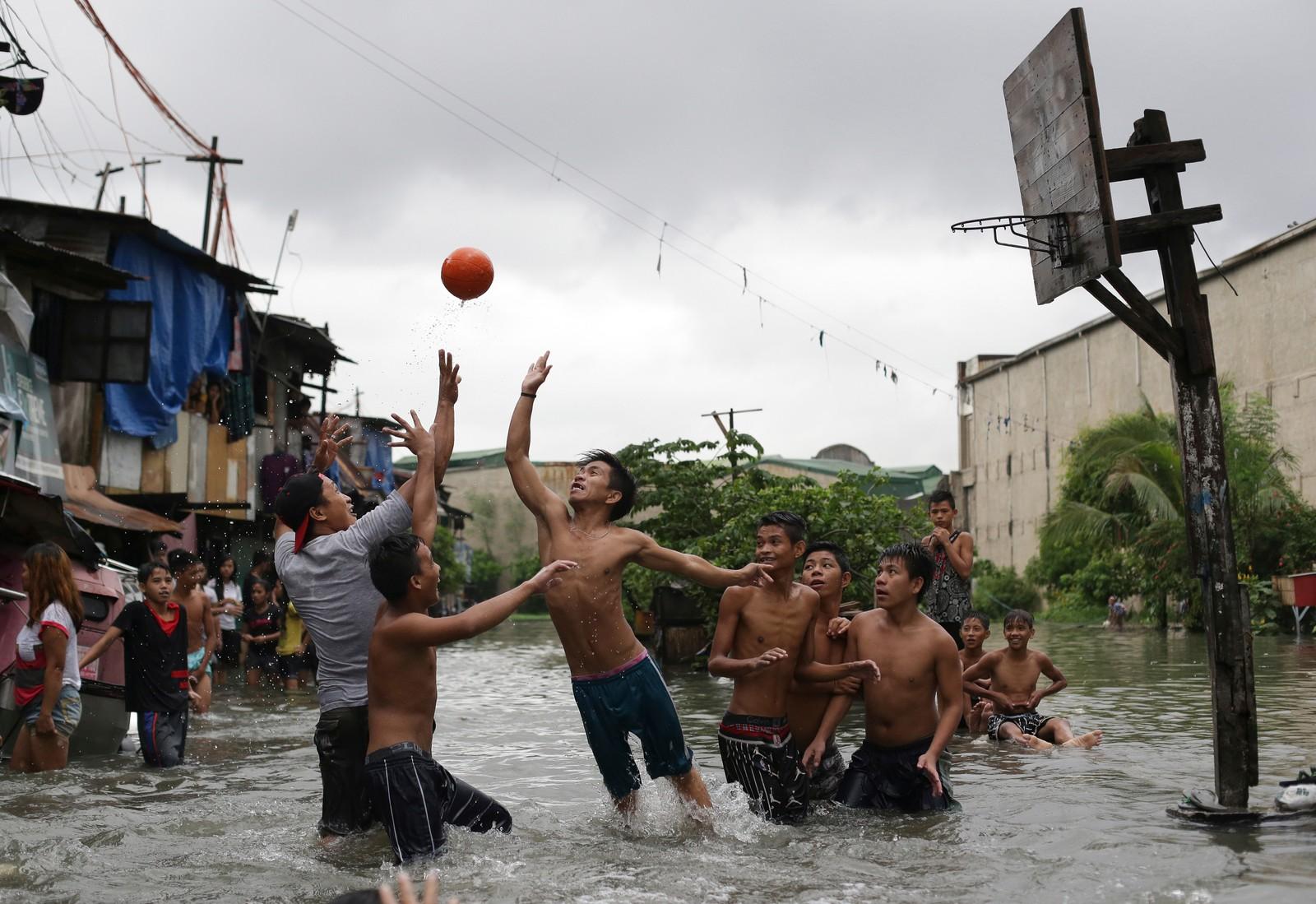 Fillippinske gutter spiller basketball i en flomrammet kystlandsby i Malabon, nord for Manila. Onsdag passerte tyfonen Chan-Hom Fillippinene, før den satte kursen mot Taiwan.