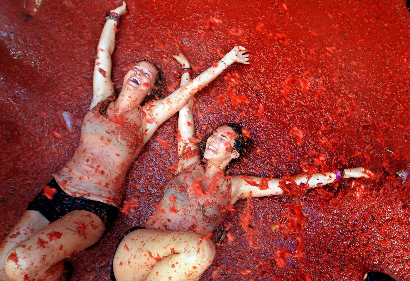 To kvinnelige deltakere ligger i et hav av knuste tomater.