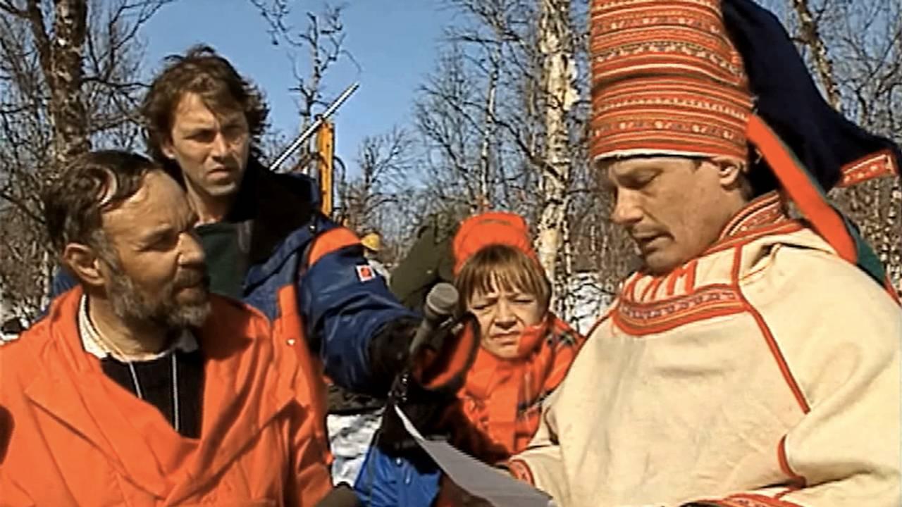 Ole Henrik Magga snakker til mann kledd i rød anorakk. Reporter og kvinne i bakgrunnen.