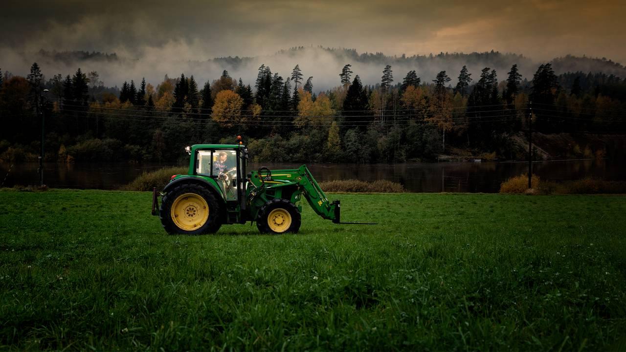 En traktor kjører over et jorde i kveldslys og med tunge skyer