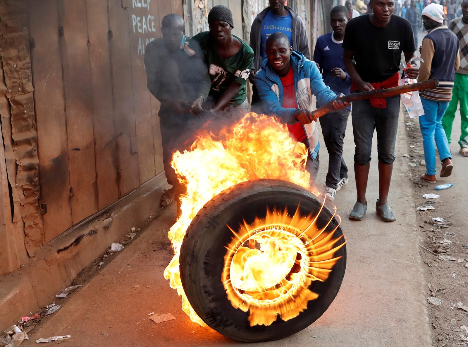 Tilhengerne til opposisjonsleder Raila Odinga tente på bildekk i Kibera-slummen i Nairobi i Kenya.