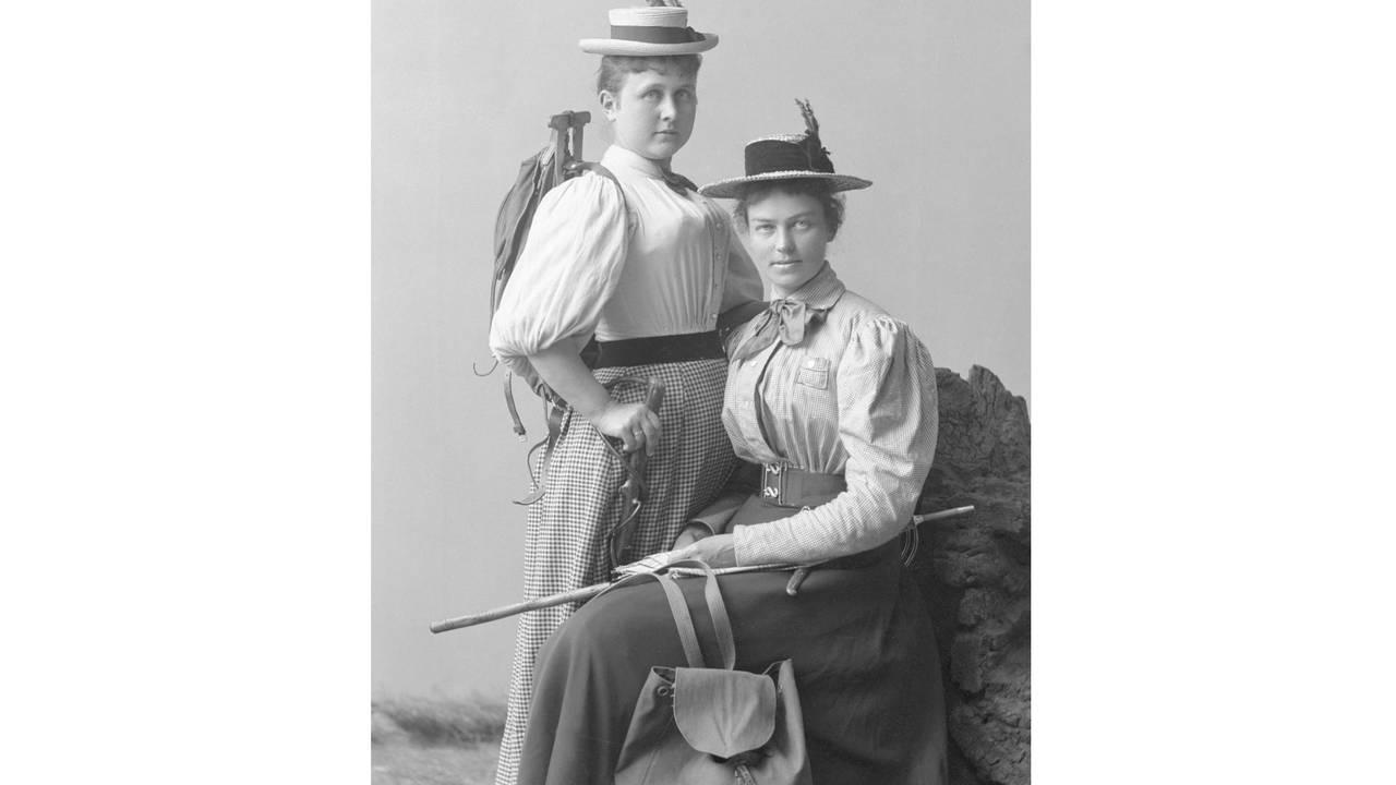 Gruppeportrett, to kvinner kledd opp til fottur. Hatt, sekk og stav.
