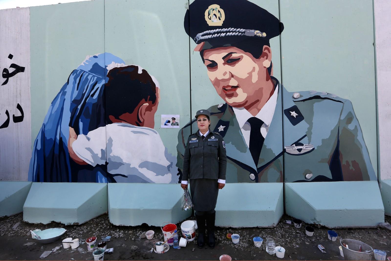 AFGHANISTAN: Friba Hameed (30) jobber som politi i Kabul i Afghanistan. Her står hun foran et portrett av henne selv, malt av en uavhengig artist utenfor politihuset.