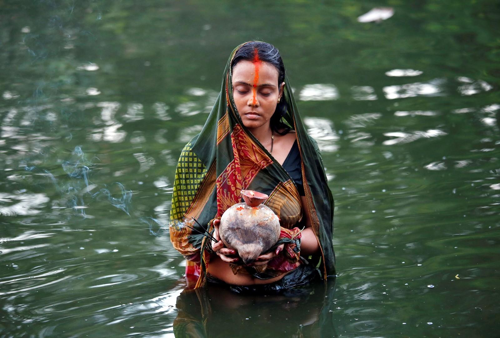 En hinduistisk kvinne holder offergaver til guden Surya under en religiøs festival i Kolkata i India.