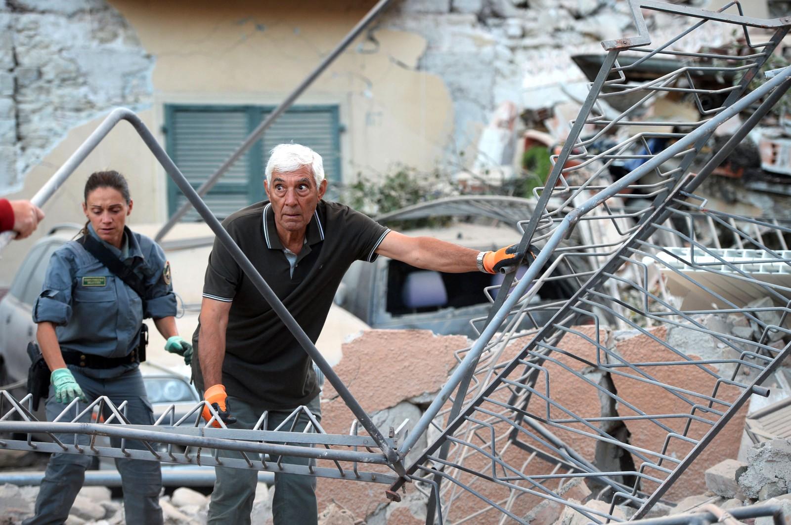 En huseier leter i ruinene sammen med en redningsarbeider.