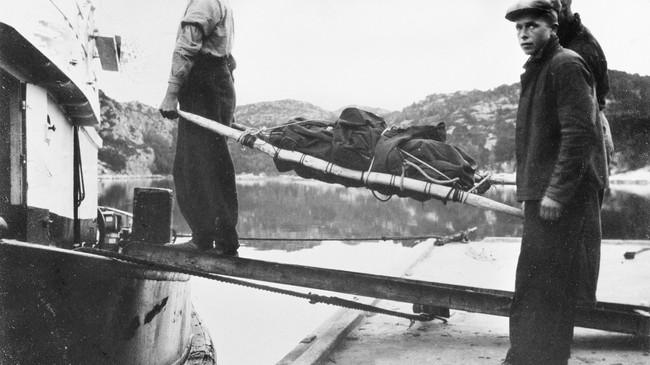 """I Hyllestad skjedde ei av dei første større flyulukkene i Noreg i 1936. Her blir ein av dei omkomne frå ulukka boren om bord i slepebåten """"Vulkanus"""", som frakta dei til Bergen. Ukjend fotograf. © Fylkesarkivet."""