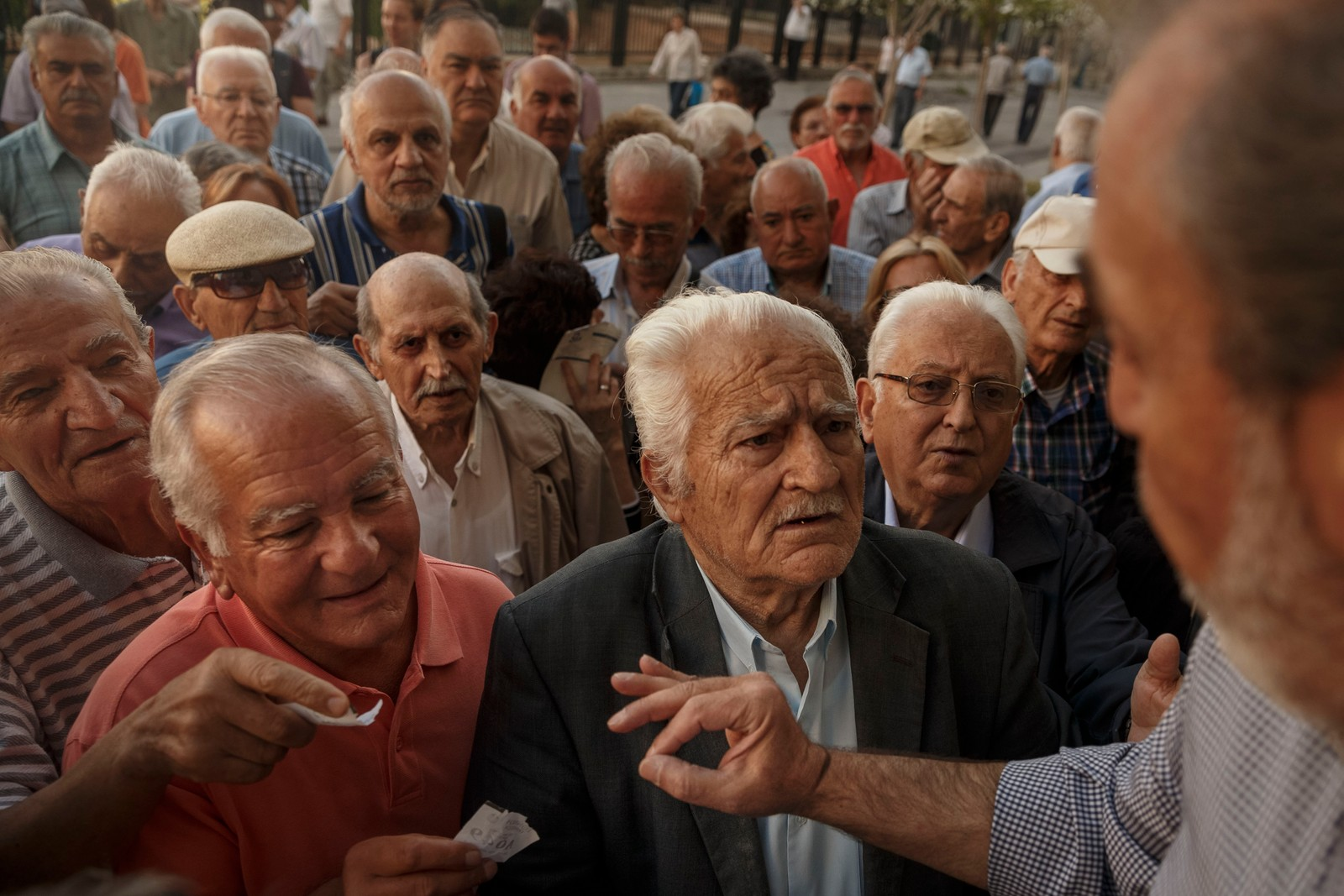 En bankansatt instruerer pensjonistene som venter utenfor til å danne en kø i henhold til nummeret på kølappene de har fått utdelt.