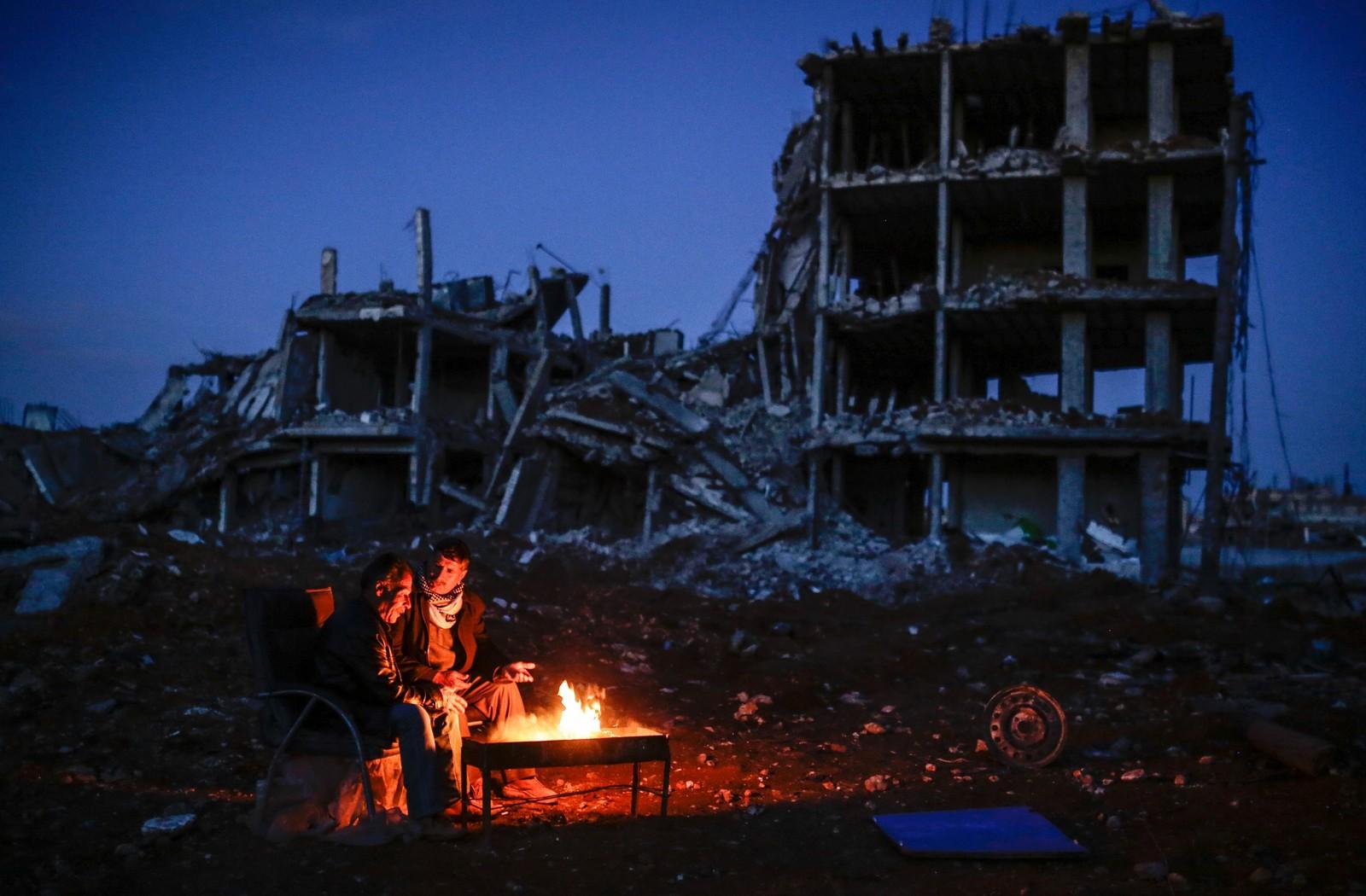 Kurdiske menn sitter rundt et bål ved siden av en ødelagt bygning i den syriske byen Kobane 22. mars.