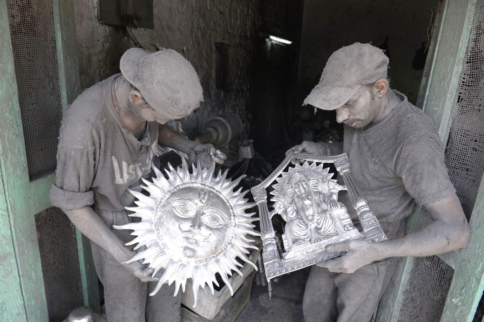 To indiske håndverkere studerer arbeidene sine på et verksted i Hyderabad i India. Metallarbeiderne i byen er berømte for statuene av hinduistiske guder. Arbeidene blir vanligvis solgt for mellom 600 og 6000 kroner.
