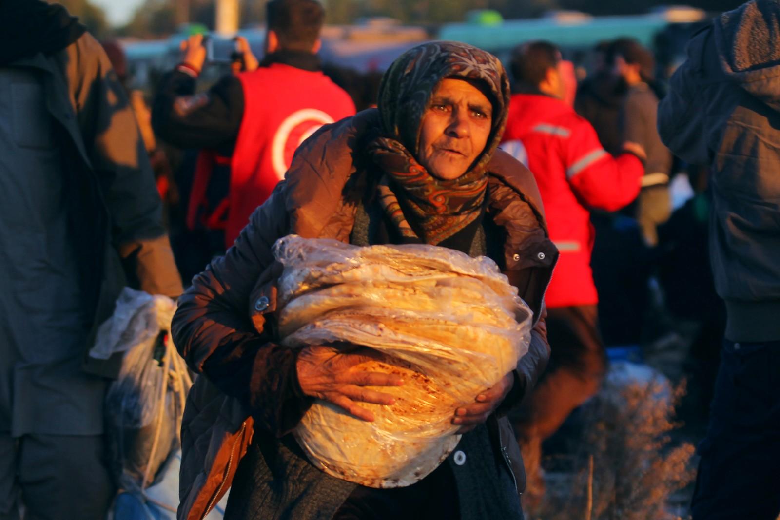 En evakuert kvinne bærer brød etter å ha sluppet ut av Aleppo.