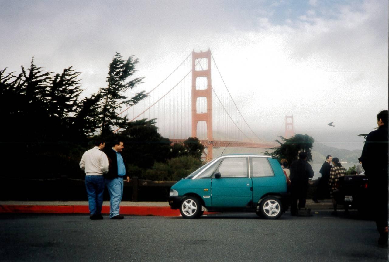 En liten norsk elbil ved den kjente brua Golden Gate Bridge i San Fransisco