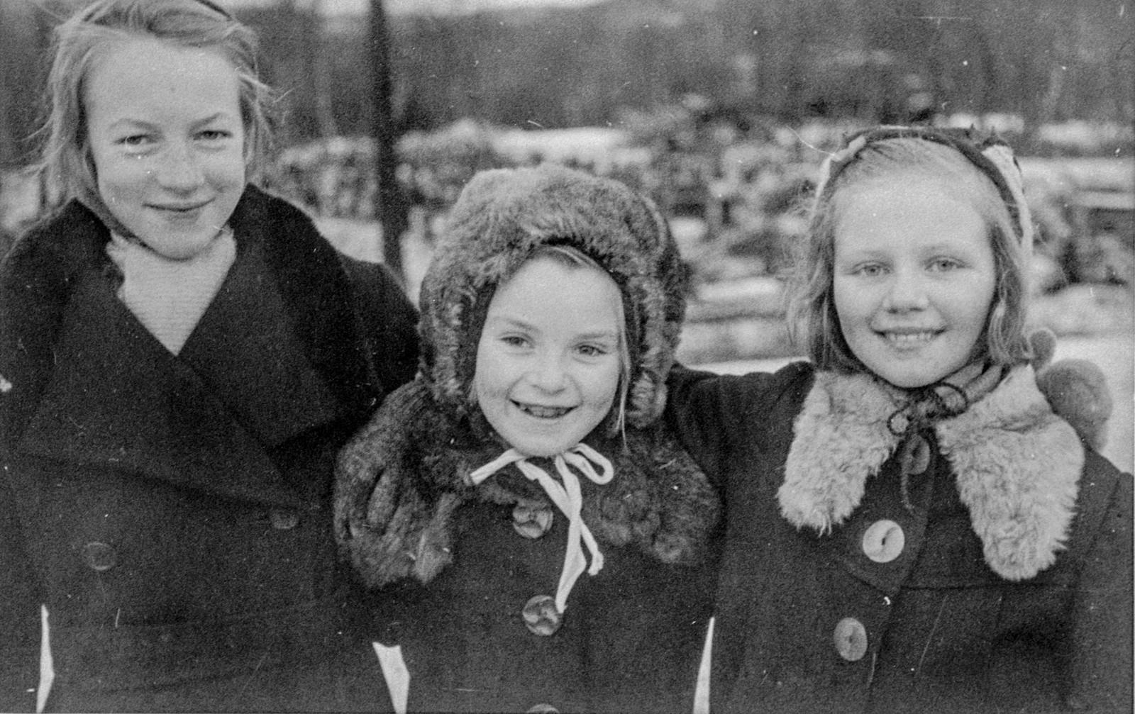 Original bildetekst: Tre småjenter fotografert etter at de hadde sett de norske troppene rykke inn i Kirkenes i begynnelsen av november 1944. De lykkelige smilene feier bort alle tegn på de strabaser som befolkningen i Kirkenes-området måtte gjennomgå før tyskerne ble jaget ut.