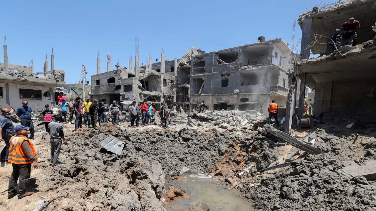 Innbyggere og redningspersonell i Gaza ser på restene av en utbombet bygning fredag 14. mai.