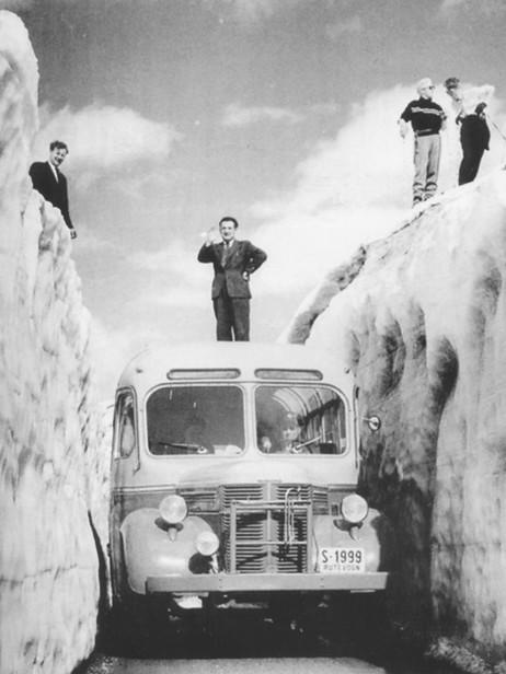 """Ein buss frå Nordfjord og Sunnmøre Billag på Tystigen ca. 1960. På taket av bussen står Ola Vik, til venstre Jakob Fure. Ukjend fotograf, frå """"Soga om Nordfjord og Sunnmøre Billag""""."""