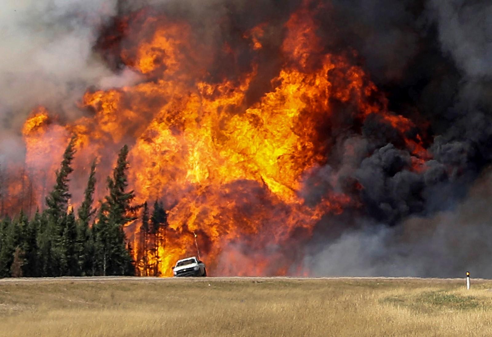 Røyk og flammer fra skogbrannen i Alberta i Canada står høyt til værs ved en bilvei ved Fort McMurray lørdag 7. mai 2016