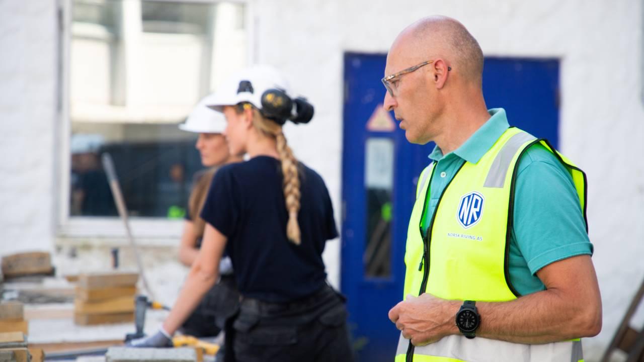 I forgrunnen står Svein Egil Dagsland i refleksvest over t-skjorten. I bakgrunnen står døtrene i arbeidstøy ved et bord med murstein.