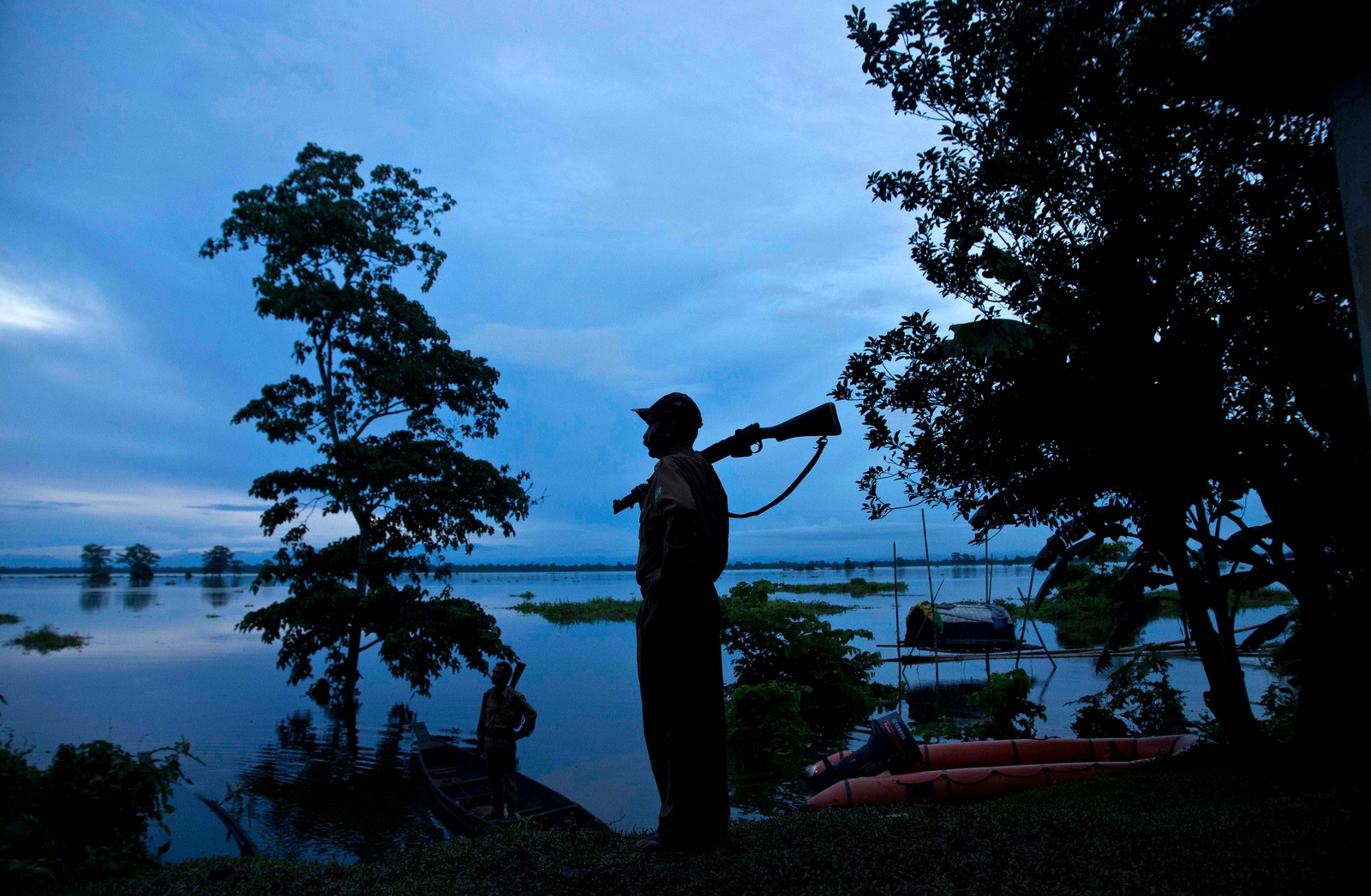 En skogvokter holder vakt ved den flomrammede nasjonalparken Kaziranga i Assam i India den 26. juli. Store deler av parken, som er hjemmet til det sjeldne panserneshornet, er under vann. Myndighetene forteller at de har funnet levningene til minst et panserneshorn som har druknet.