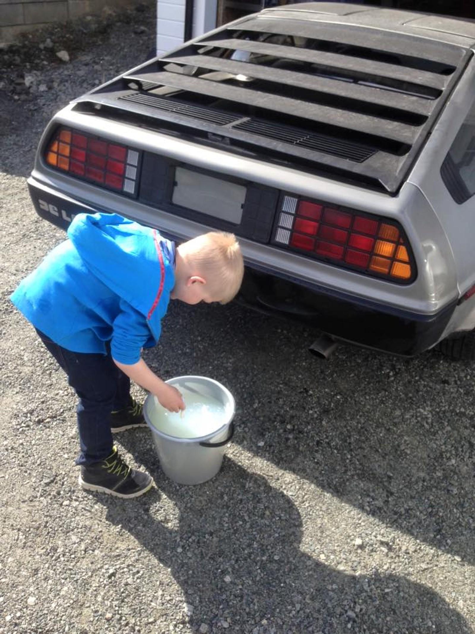 Stian Birkeland får hjelp av sønnen til å ta vasken på DeLorean-bilen som snart skal bli klar for veien igjen etter en motorskade.