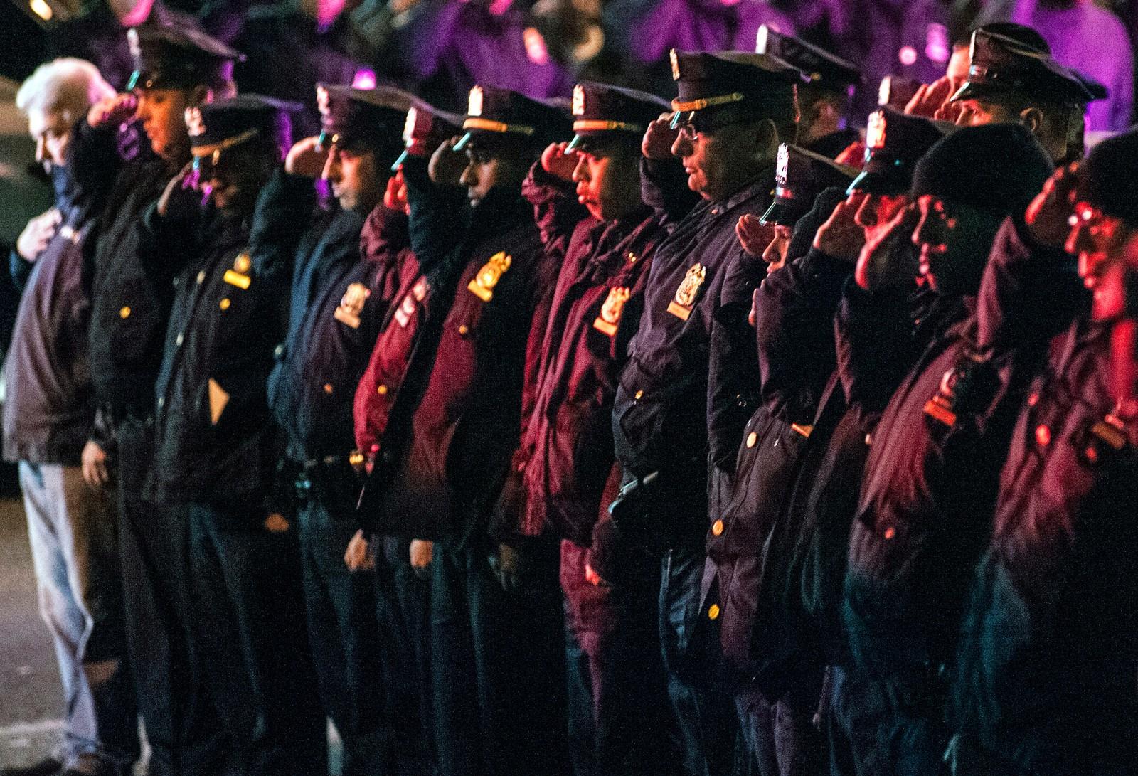 New York-politiet gjør honnør langs ruten der kroppene til de to døde politimennene fraktes.
