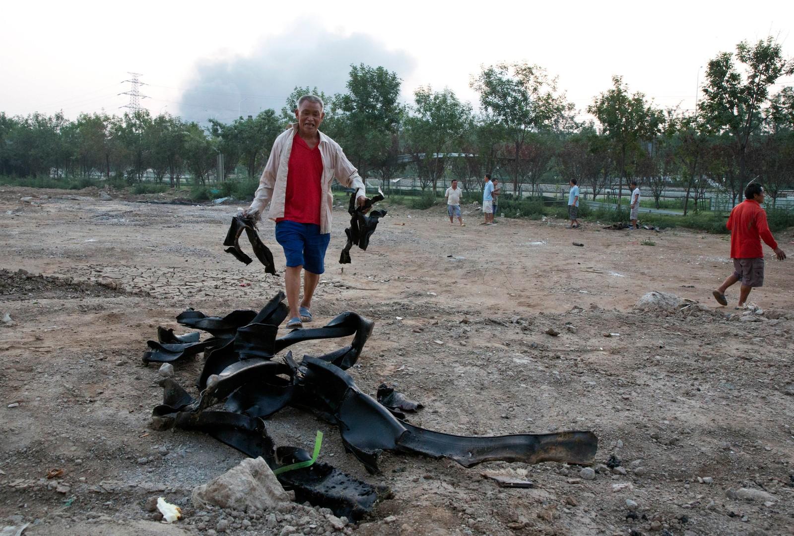 RYDDER: En mann prøver å rydde opp etter at metallgjenstander ble spredd ut over et stort område under eksplosjonene.
