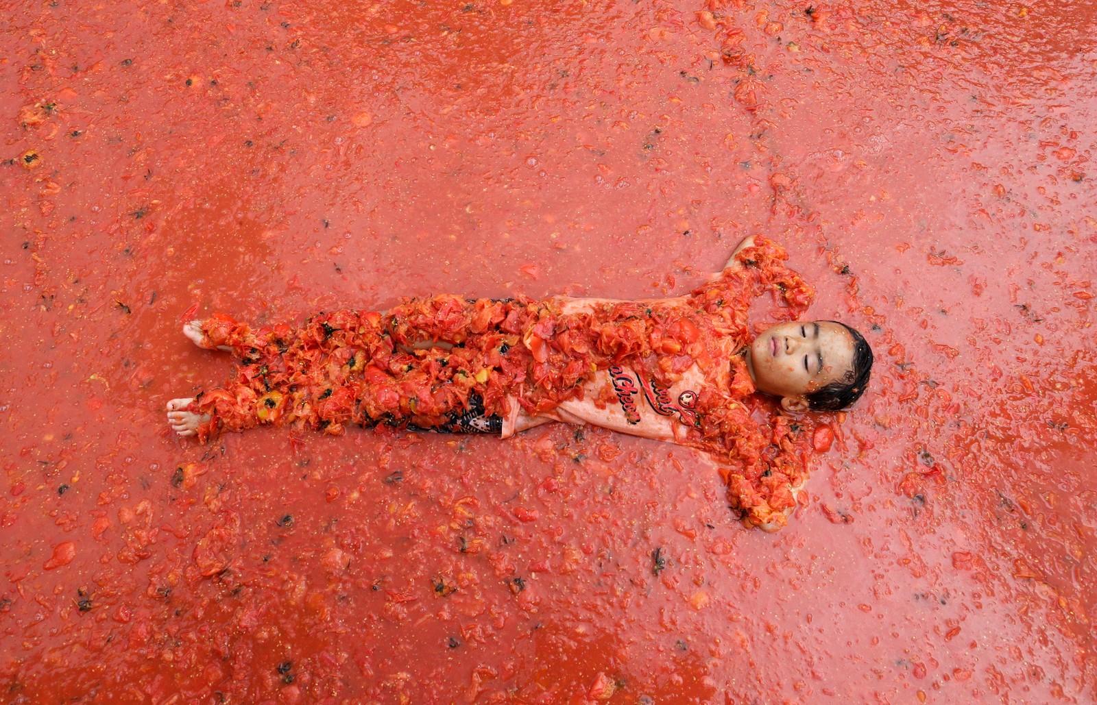 En gutt ligger i en liten tomatrød innsjø under tomatfestivalen i Hwacheon i Sør-Korea, som ble arrangert forrige helg.