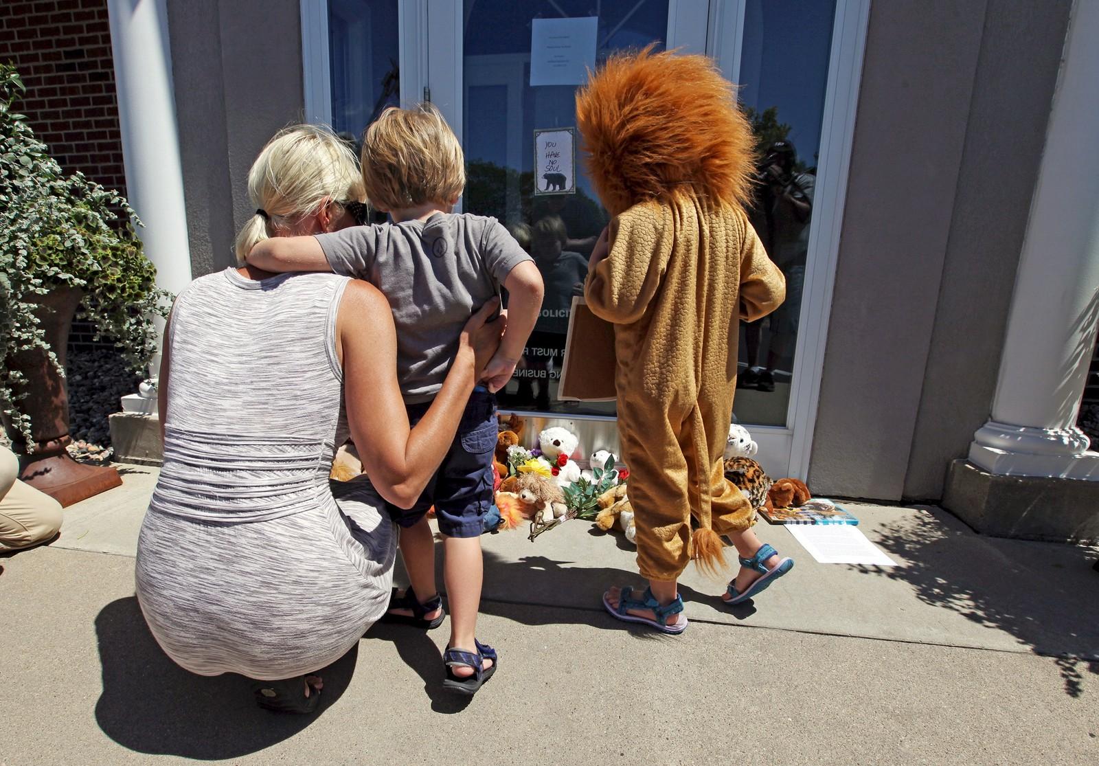 Minnesota: Sarah Madison holder rundt sin sønn Beckett (3), mens datteren Quinn (5), kledd i løvekostyme, ser på alle bamsene og hilsenene i forbindelse med drapet på kjendisløven Cecil. Drapet har skapt reaksjoner verden rundt og tannlegen som skjøt løven omtales nå som «en av de mest forhatte mennene på internett».