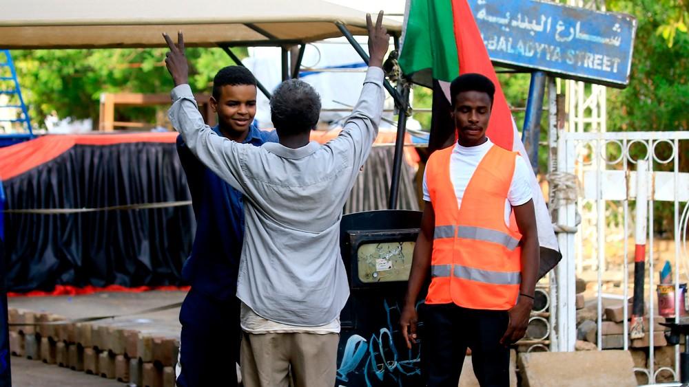 Demokratiaktivist i Sudan sjekker en mann som vil inn i leiren deres
