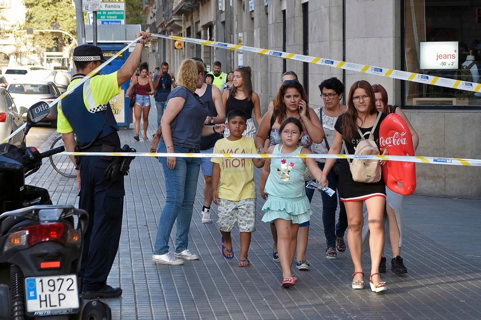 EVAKUERES: Personer evakueres fra området, etter at en varebil kjørte inn i en folkemengde i Las Ramblas i Barcelona.