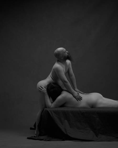 En kraftig bygd mann ligger på magen på en svart madrass. Han har ansiktet sitt foran skrittet til en skallet mann med skjegg og simulerer oralsex. Begge er nakne, men kjønnsorganene er ikke synlige.