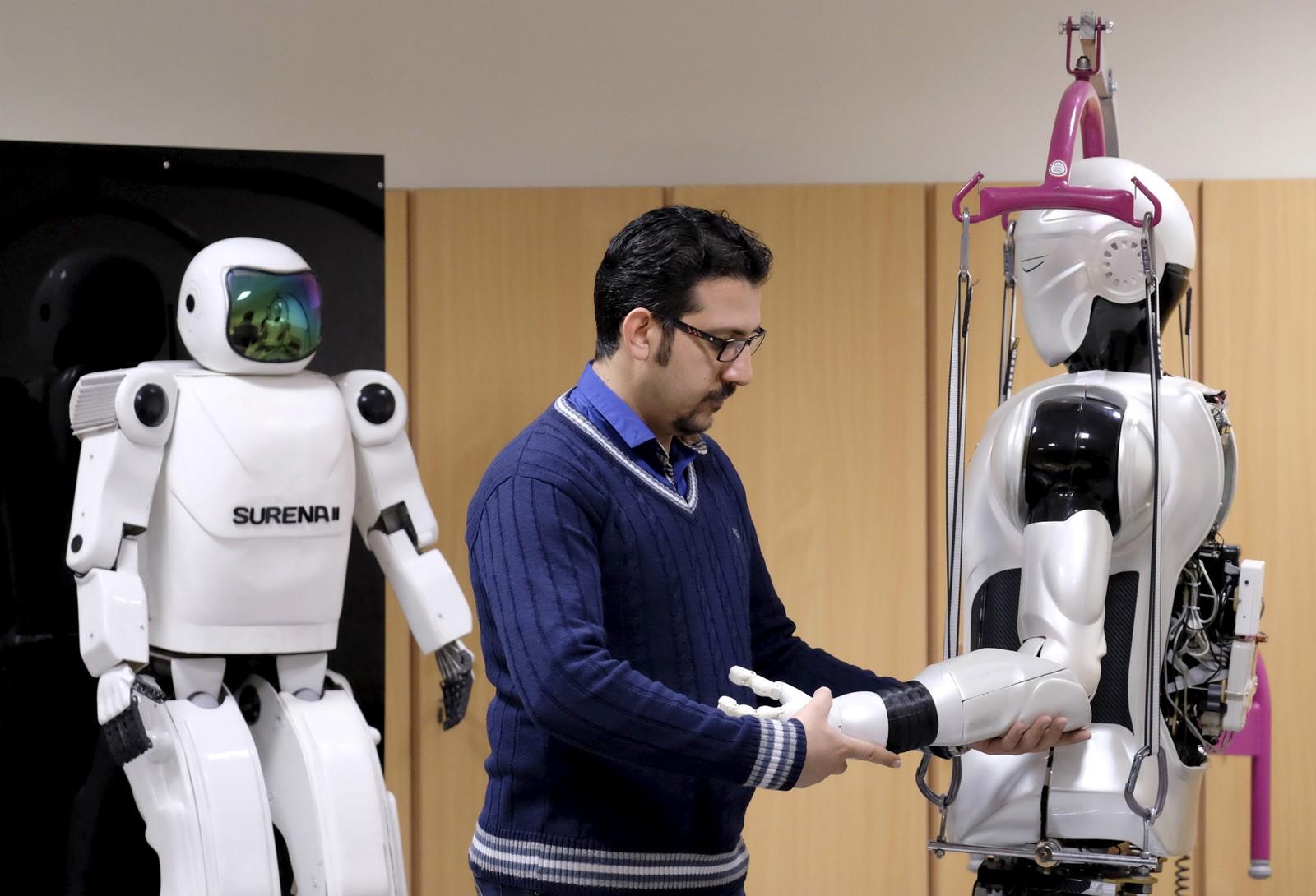 En ingeniør jobber med den menneskelignende roboten Surena 3 mens forgjengeren Surena 2 «følger med» i bakgrunnen. Universitetet i Teheran har utviklet denne 98 kilo tunge roboten som blant annet kan bevege seg i ujevnt terreng og gjenkjenne ansikter.