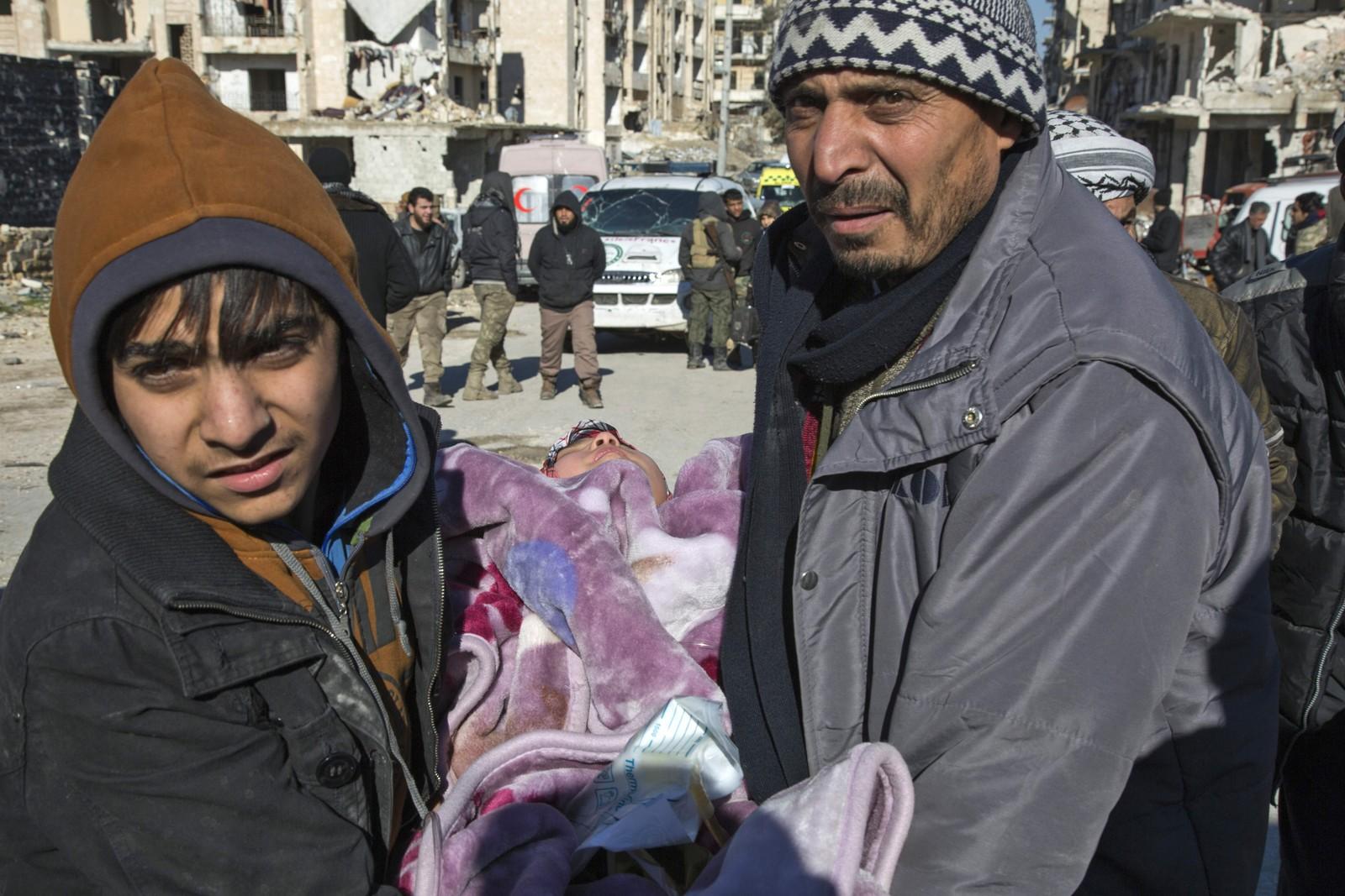 Et syrisk barn bæres ut under evakueringen i Aleppo.