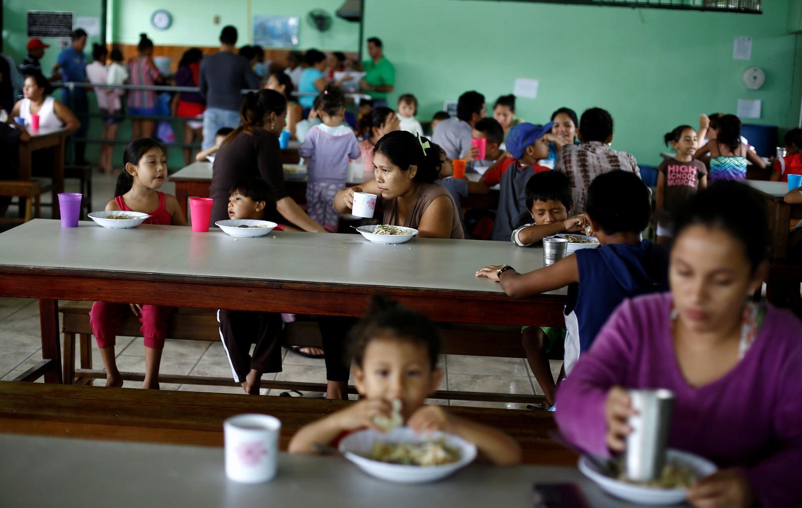 Hjelpearbeidarar serverer mat til familiane som har kome til ein skule i Guapiles i Costa Rica.