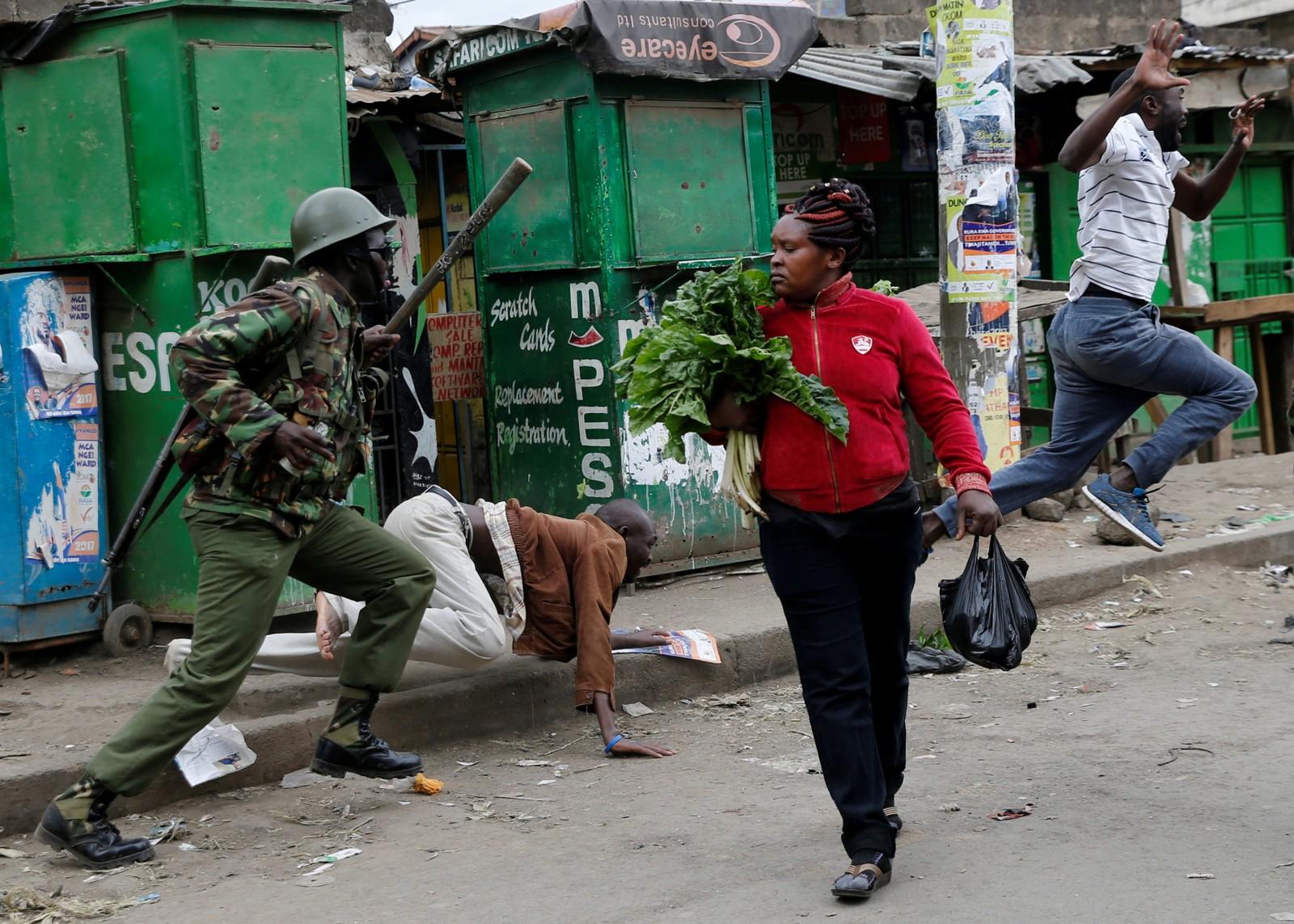En kvinne er på vei hjem med grønnsakene hun har kjøpt mens opprørspoliti forsøker å spre demonstranter i Mathare i Nairobi i Kenya. Minst seks personer er drept i opptøyer etter beskyldninger om valgfusk i etterkant av valget tirsdag.