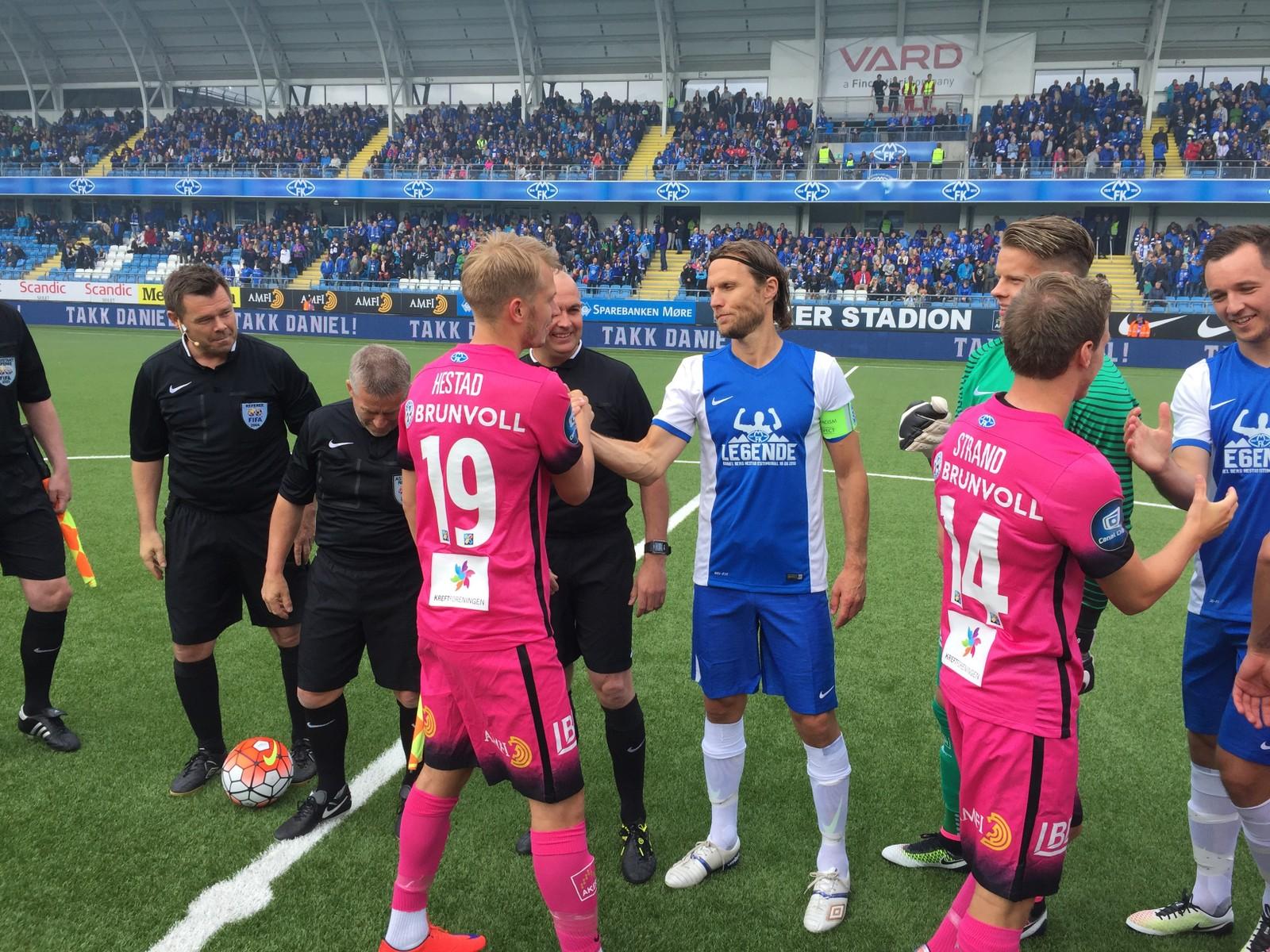 KLAR: Spillerne tar hverandre i hånden før kampen skal starte.