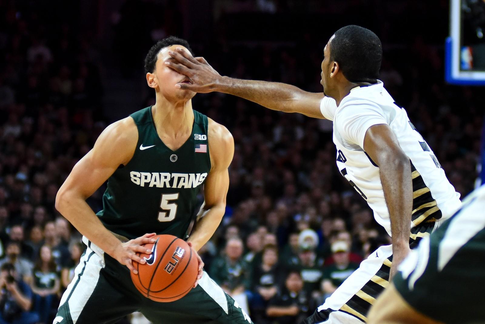 College-basketball mellom Michigan og Oakland.  Oakland Golden Grizzlies-spiller Martez Walker bruker et noe skittent triks for å forsvare seg mot Michigan State Spartans' Bryn Forbes.