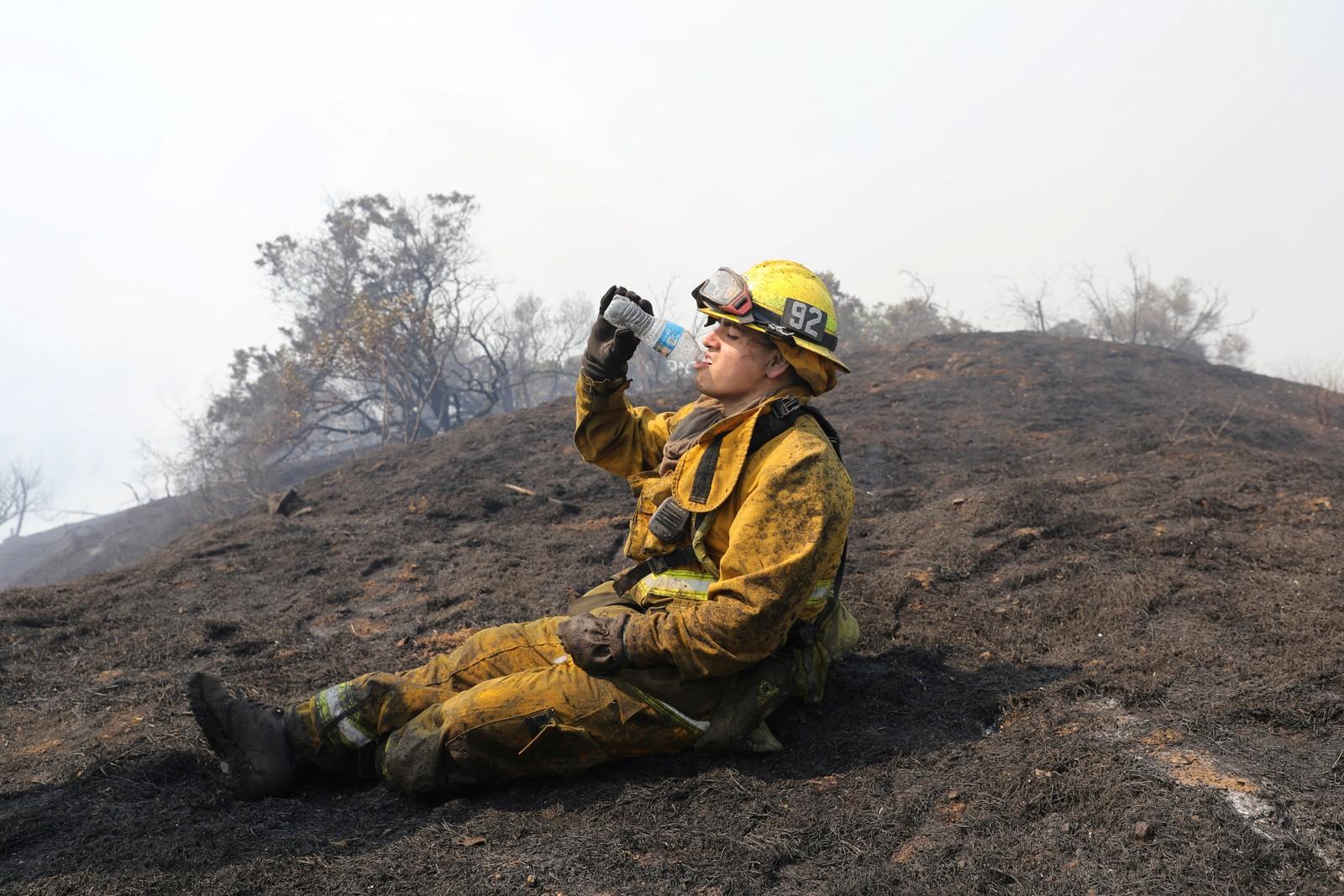 En brannmann tar seg en vannslurk og en pust i bakken under slokkearbeid i Mandeville Canyon i Los Angeles.