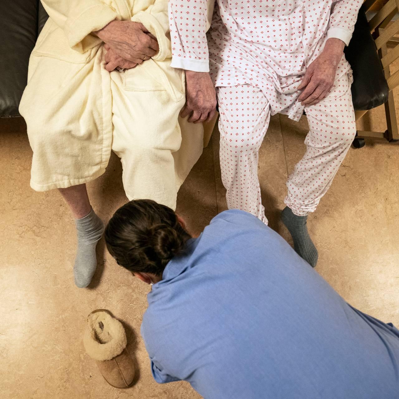 Ekteparet sitter i sofaen i pysj med tøfler på. En pleier hjelper med å ta på tøfler.