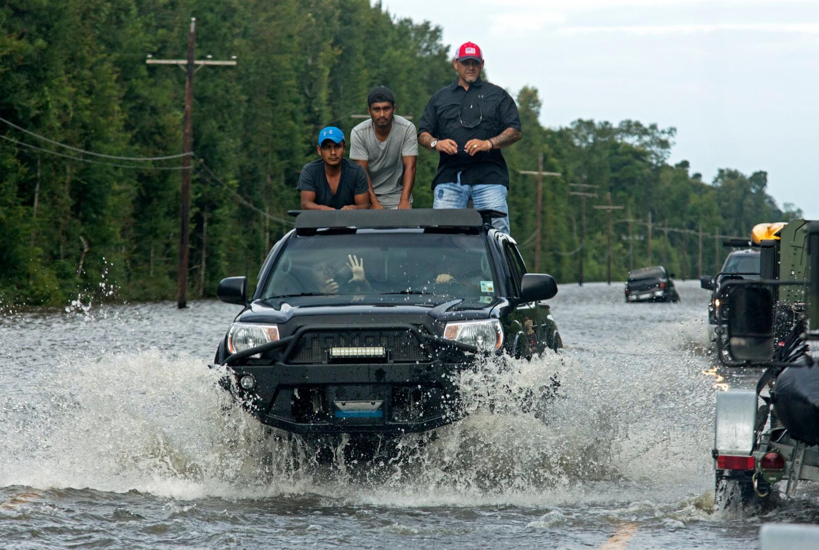 MOTORVEI: Bilene kjører gjennom flomvannet som ligger på motorvei 190 i Holden, Louisiana.